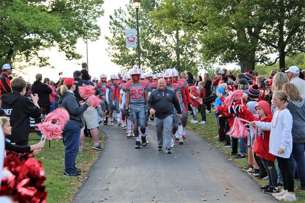 Football players enter stadium on Homecoming